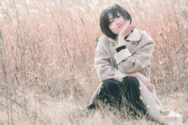 Ritratto della donna di stile che si siede in mezzo al campo a lamella