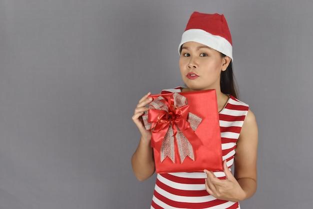 Ritratto della donna felice che porta il cappello del babbo natale e che tiene il contenitore di regalo.