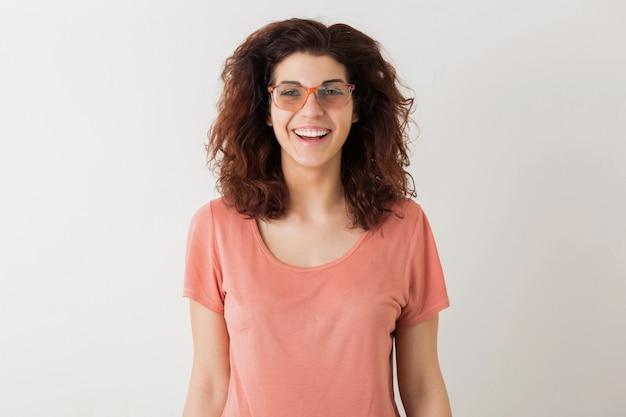 Ritratto della donna graziosa dei giovani pantaloni a vita bassa felici naturali con l'acconciatura riccia in camicia rosa che posa i vetri d'uso isolati, umore positivo