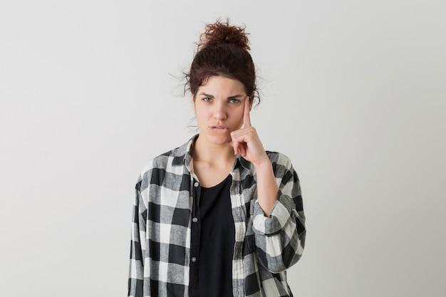 Ritratto della donna graziosa dei giovani pantaloni a vita bassa in camicia a quadretti che pensa, avendo un problema, posare isolato