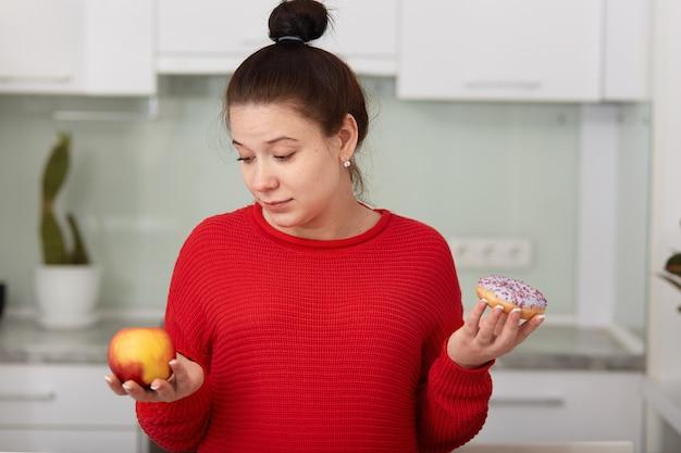 Ritratto della donna incinta che decide di scegliere alimento sano o malsano, posante sull'interno bianco della cucina