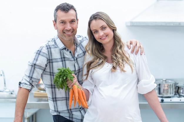 Ritratto della donna incinta che esamina macchina fotografica mentre tenendo le carote