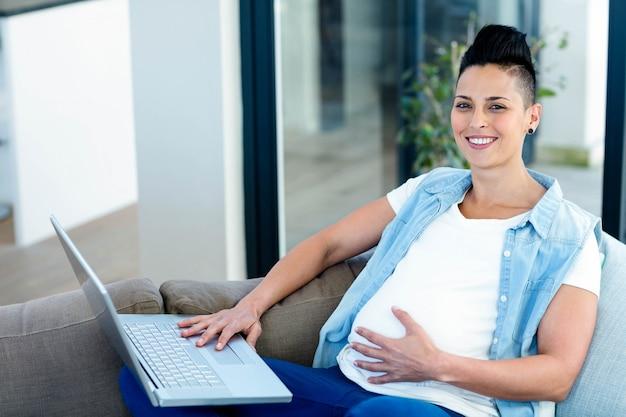 Ritratto della donna incinta che utilizza computer portatile mentre rilassandosi sul sofà nel salone