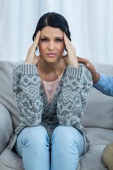 Ritratto della donna incinta preoccupata che si siede sul sofà a casa