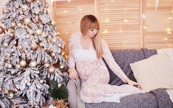 Ritratto della donna incinta, vibrazioni del nuovo anno. Affascinante donna bionda attesa si siede