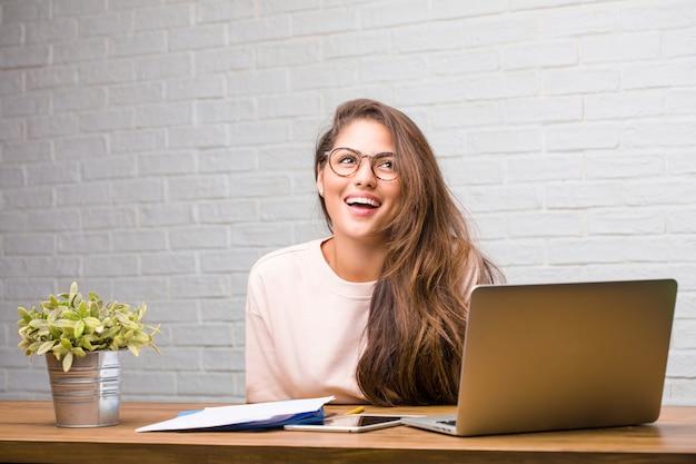 Ritratto della donna latina del giovane studente che si siede sul suo cercare dello scrittorio