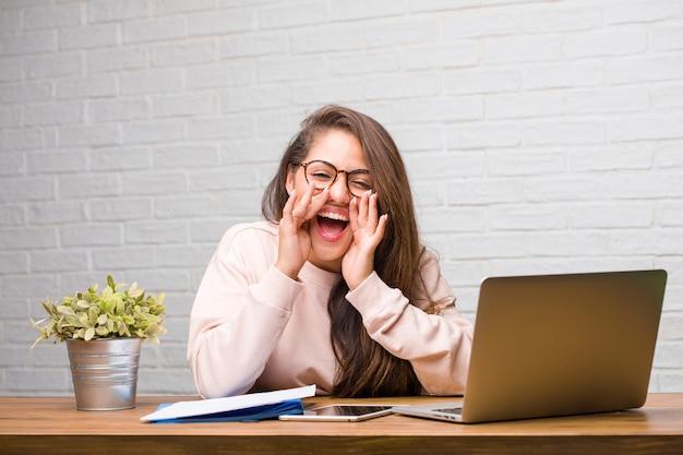 Ritratto della donna latina del giovane studente che si siede sul suo scrittorio che grida felice