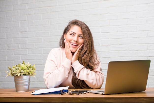 Ritratto della donna latina del giovane studente che si siede sul suo scrittorio sorpreso e colpito