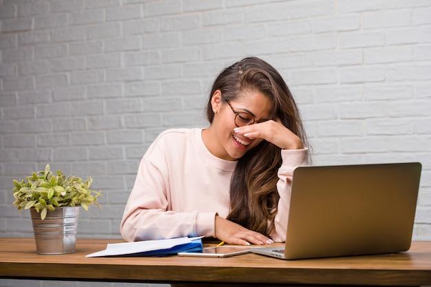 Ritratto della donna latina del giovane studente che si siede sulla sua scrittorio che ride e che si diverte