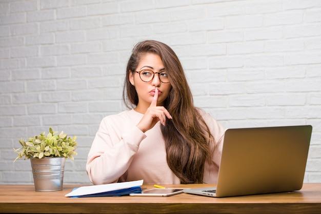 Ritratto della donna latina del giovane studente che si siede sulla sua scrivania che tiene un segreto o che chiede il silenzio