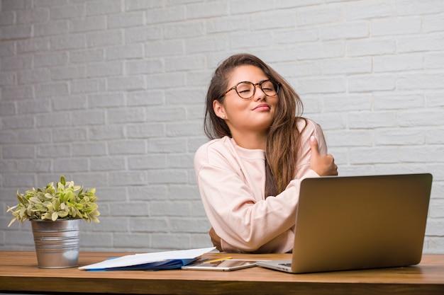 Ritratto della donna latina del giovane studente che si siede sulla sua scrivania fiera e sicura