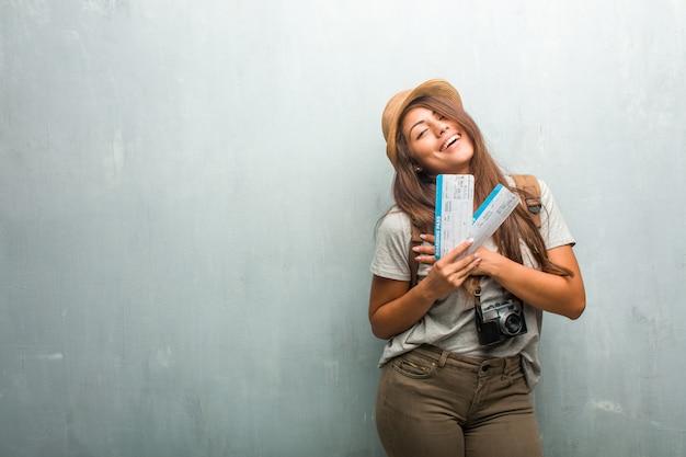 Ritratto della donna latina del giovane viaggiatore contro una parete che fa un gesto romantico