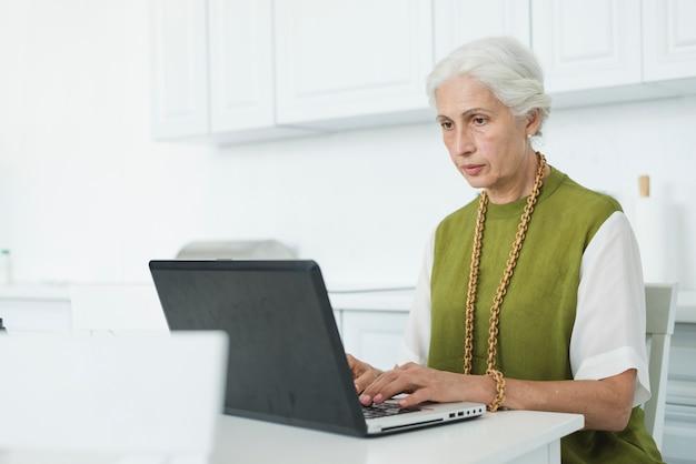 Ritratto della donna maggiore che per mezzo del computer portatile
