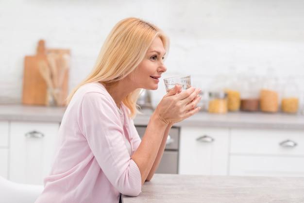 Ritratto della donna matura che beve un bicchiere d'acqua