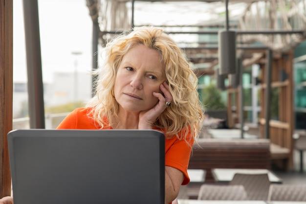 Ritratto della donna matura pensierosa che lavora al computer portatile in caffè