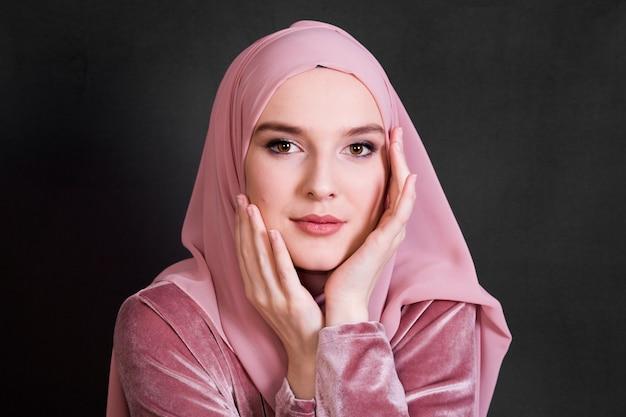 Ritratto della donna musulmana che propone sulla priorità bassa nera
