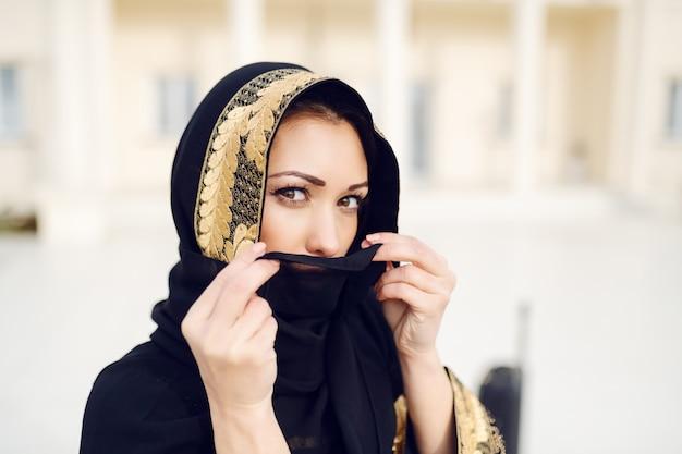 Ritratto della donna musulmana splendida che sta all'aperto e che nasconde il suo fronte con la sciarpa mentre esaminando macchina fotografica.