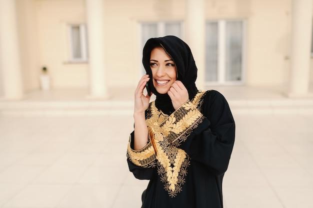 Ritratto della donna musulmana splendida con il sorriso a trentadue denti che sta all'aperto.