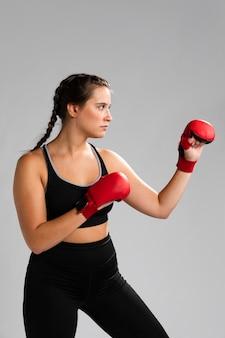 Ritratto della donna obliqua che perfora con i guanti della scatola