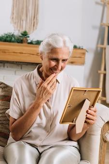 Ritratto della donna senior allegra che si siede sul sofà che esamina la struttura della foto