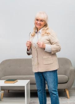 Ritratto della donna senior bionda sorridente che sta nel salone che esamina macchina fotografica