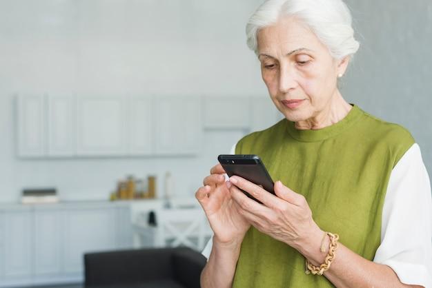 Ritratto della donna senior che manda un sms sul telefono cellulare a casa