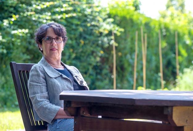 Ritratto della donna senior con i vetri che si siedono nel giardino
