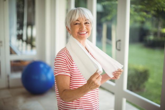 Ritratto della donna senior con l'asciugamano a casa