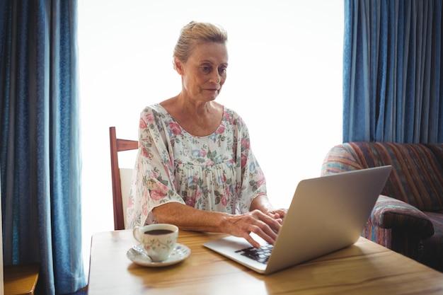 Ritratto della donna senior concentrata che per mezzo di un computer portatile