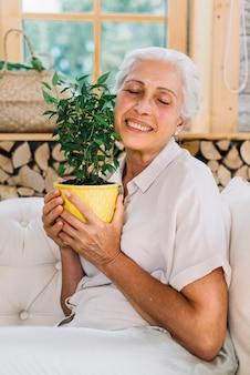 Ritratto della donna senior felice che ama la sua pianta da vaso