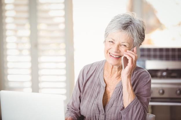 Ritratto della donna senior felice che parla sul telefono cellulare