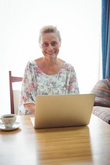 Ritratto della donna senior sorridente che per mezzo di un computer portatile