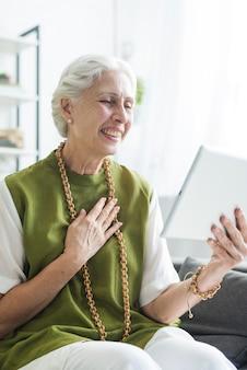 Ritratto della donna senior sorridente che si siede sul sofà che esamina compressa digitale