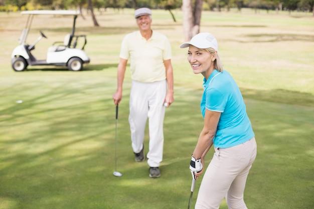 Ritratto della donna sicura del giocatore di golf dall'uomo