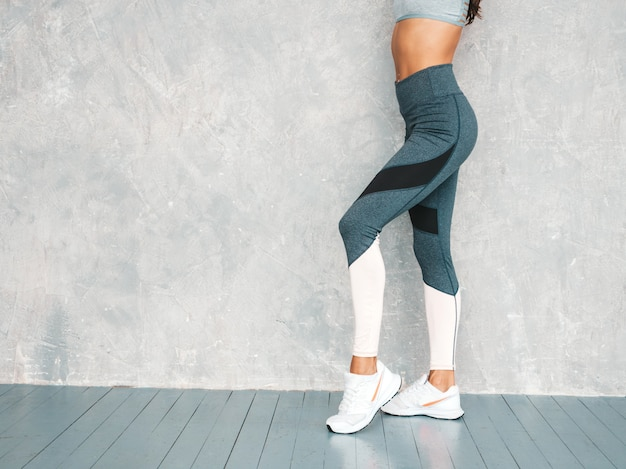 Ritratto della donna sicura di forma fisica in abbigliamento sportivo che sembra sicuro. femmina che posa nello studio vicino alla parete grigia