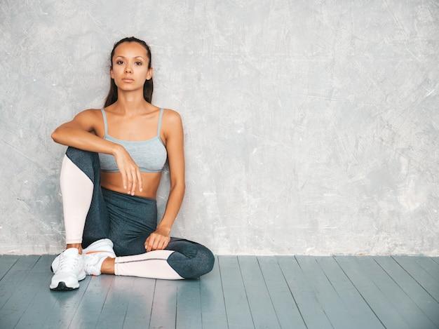 Ritratto della donna sicura di forma fisica in abbigliamento sportivo che sembra sicuro. femmina che si siede nello studio vicino alla parete grigia