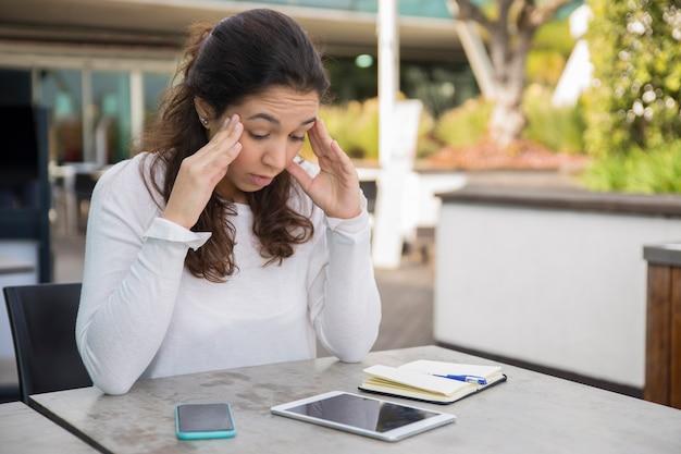 Ritratto della donna sollecitata che si siede alla tavola con la compressa digitale