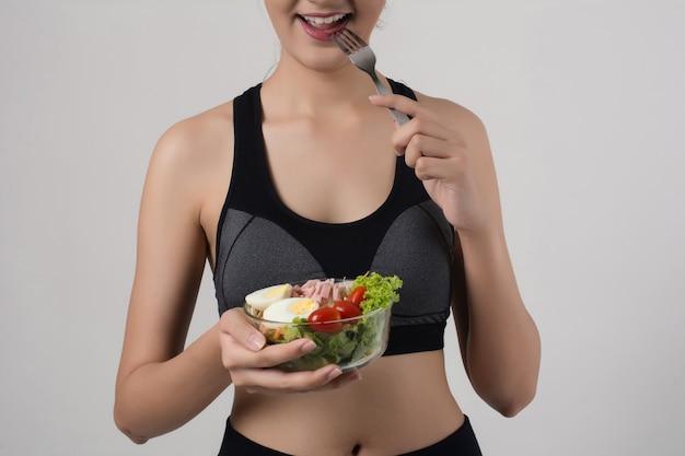 Ritratto della donna sorridente attraente che mangia insalata isolata su fondo bianco.