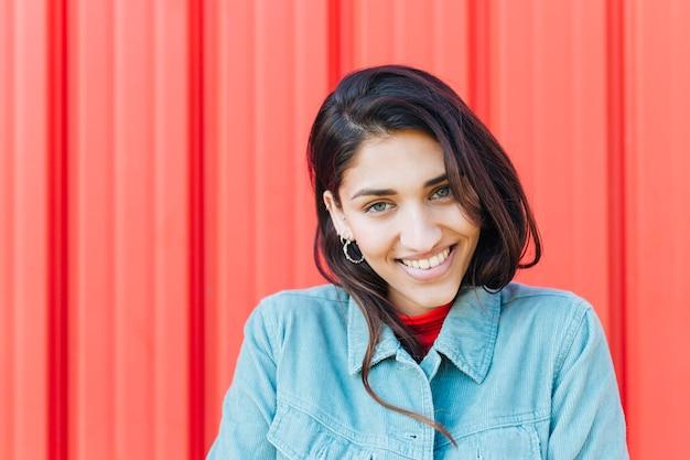 Ritratto della donna sorridente che esamina macchina fotografica davanti al contesto rosso