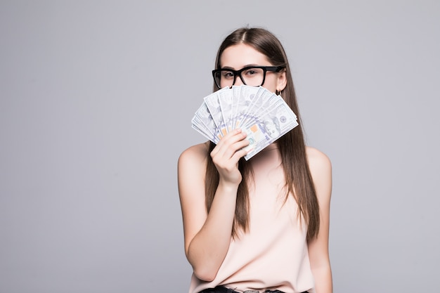 Ritratto della donna sorridente che giudica i dollari isolati sopra la parete grigia