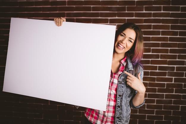 Ritratto della donna sorridente che tiene cartello in bianco