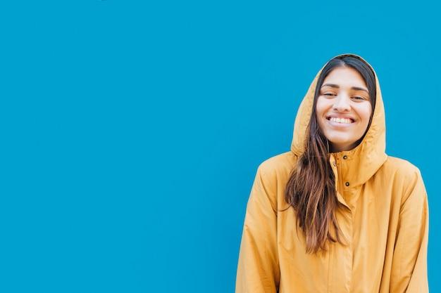 Ritratto della donna sorridente contro fondo blu con lo spazio della copia