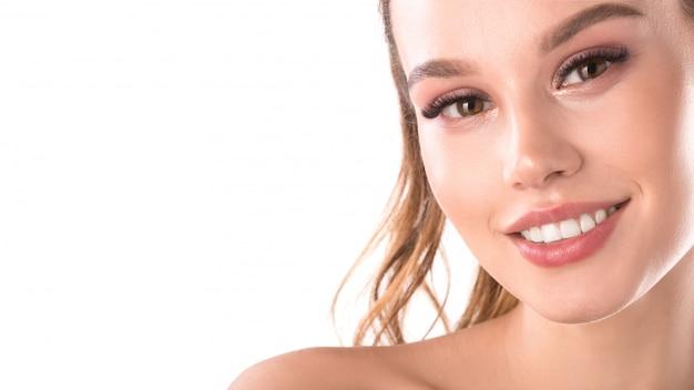 Ritratto della donna sorridente graziosa con i denti bianchi perfetti con spazio per testo. giovane bello modello femminile caucasico con il sorriso sano che posa nello studio sopra la parete bianca.