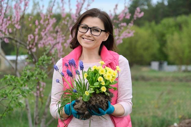 Ritratto della donna sorridente matura nel giardino di primavera