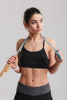 Ritratto della donna sportiva che osserva da parte e che tiene la corda di salto sul suo collo, isolato sopra la parete grigia