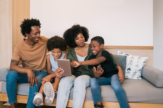 Ritratto della famiglia afroamericana che prende un selfie insieme alla tavoletta digitale a casa. concetto di famiglia e stile di vita.