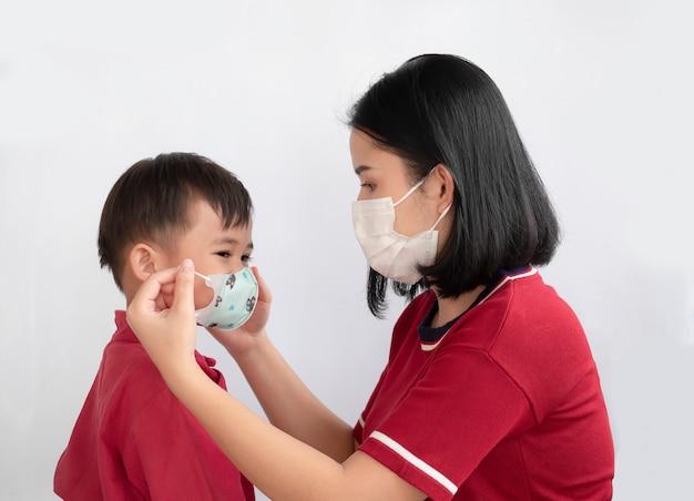Ritratto della famiglia asiatica che mostra amore e che indossa maschera protettiva