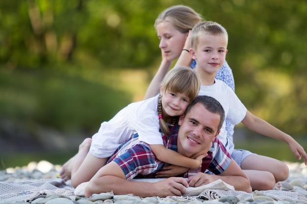 Ritratto della famiglia di giovane madre felice, padre e due bambini biondi svegli, ragazzo e ragazza il giorno di estate luminoso con bokeh verde. felici rapporti familiari, amore, cura e perfetto concetto di vacanza
