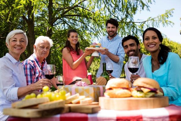 Ritratto della famiglia felice che mangia i bigné e vino rosso in parco