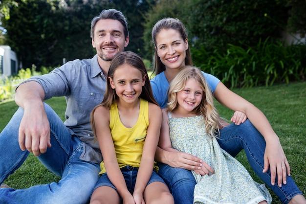 Ritratto della famiglia felice che si siede in un giardino